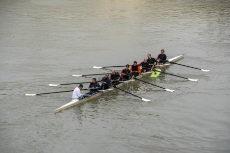 Rome, Italy - November 19, 2016: Males rowing team in race on the Tiber River. Teamwork concept. Strong business conceptual background