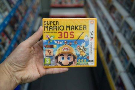 Foto de Bratislava, Eslovaquia, circa abril de 2017: hombre con Super Mario Maker videojuego en la consola de Nintendo 3ds en la tienda - Imagen libre de derechos