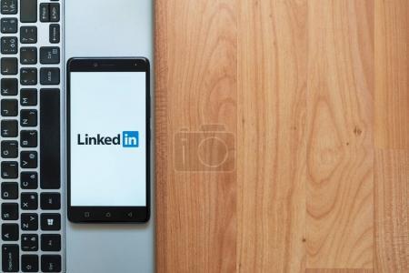 Photo pour Los Angeles, Usa, 18 juillet 2017: Linkedin logo sur l'écran du smartphone placé sur l'ordinateur portable sur fond en bois. - image libre de droit