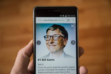 Photo for London, december 31, 2017: Bill Gates on forbes website, mobile phone version. Hand holding smartphone with wooden background - Royalty Free Image