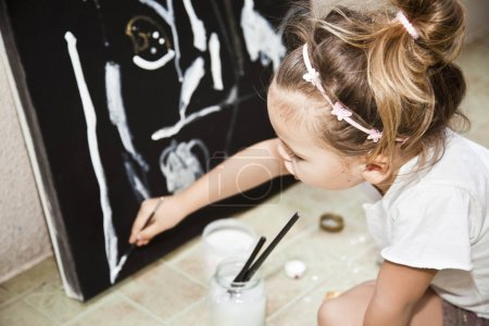 Little girl draws a picture of acrylic