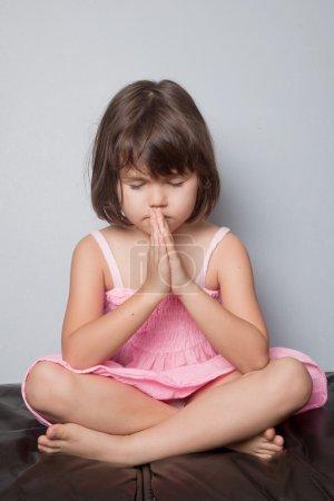 Little girl praying in lotus position