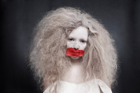 Young woman with red tape on mouth