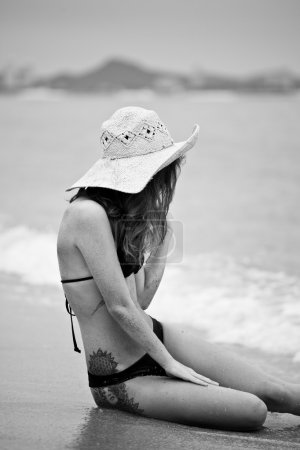 Photo for Beautiful woman sitting on sand beach - Royalty Free Image
