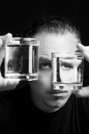 Photo for Multiple personality disorder concept. Man with two glasses of liquid with the reflection of his face - Royalty Free Image