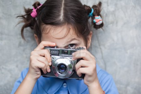 Little girl with a film camera