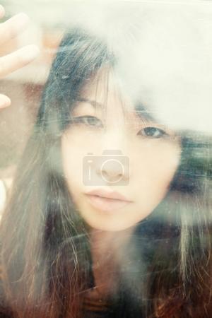 Sensual japanese girl behind glass