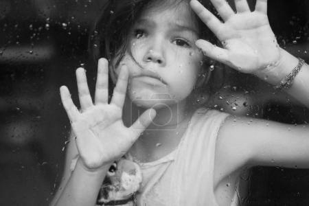 sad preteen girl looking through glass