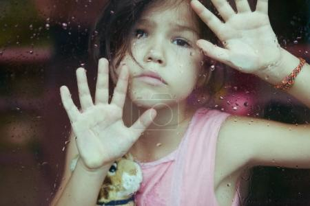 sad preteen girl looking through glass