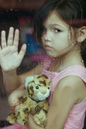 girl sitting near window with toy