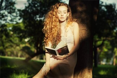 The woman with curly hair reading a book in the autumn park