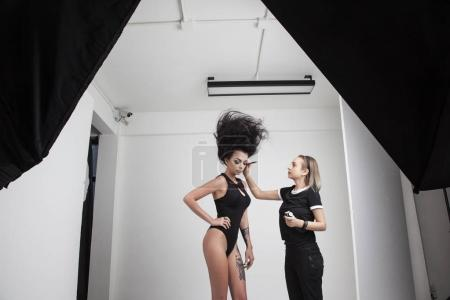 brunette model posing in sexy underwear and make up artist standing on studio background