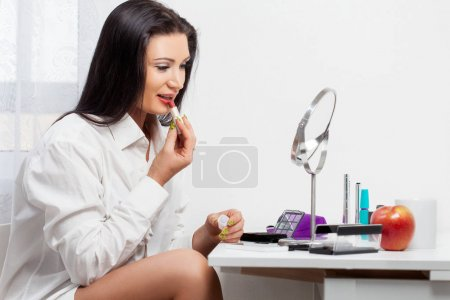 young woman paints her lips