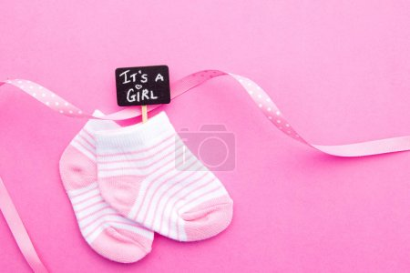 Baby Girl - pink and white socks with ribbon on pink background with It's a Girl blackboard sign