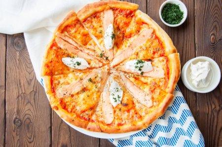 Photo pour Pizza au poisson et fromage à la crème - Plaisir sur fond de bois. Vue du dessus . - image libre de droit