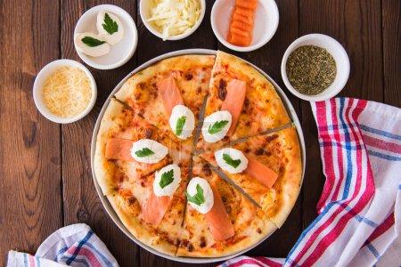 Photo pour Pizza maison au saumon et fromage à la crème - Plaisir. Ingrédients alimentaires dans un bol. Vue de dessus. Pose plate . - image libre de droit
