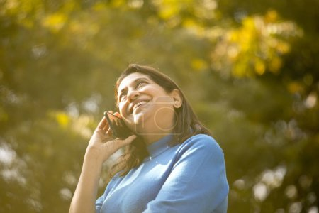 Happy senior woman using phone at park outdoor...