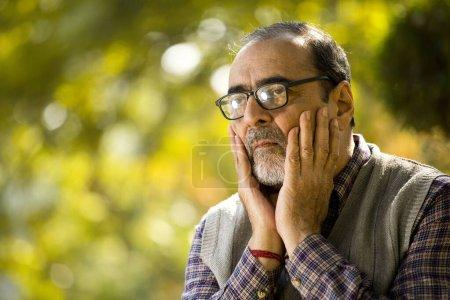 Photo pour Un homme âgé en pensées profondes au parc - image libre de droit