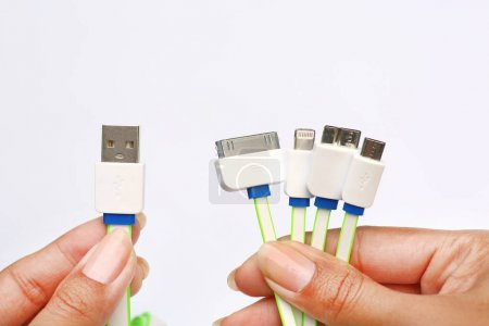 Hands holding many type adapter in 1 USB Charger on white background. universal Charger