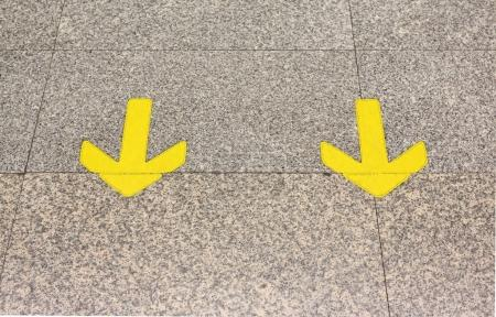 Yellow arrow sign indicate on marble floor