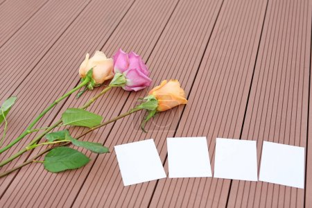 Empty notepaper with rose flower on wooden.