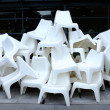 A lot of white plastic chairs arranged in a pile....