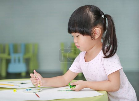 Cute asian child girl painting with paintbrush and water colors.