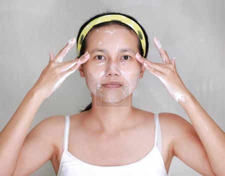 Woman applying foam cream to face in bathroom