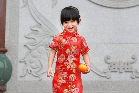 Cute asian kid girl in Traditional Chinese dress with holding sacred Orange at chinese temple in bangkok thailand.