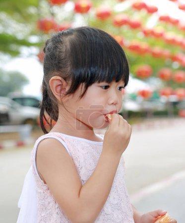 Cute asian kid girl eating orange fruit at chinese temple in bangkok thailand.