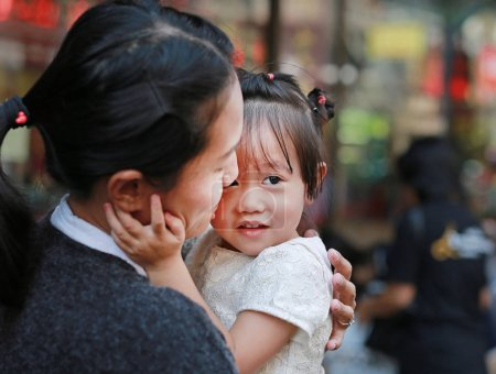portrait of mother and cute little girl in Yaowarat Road (Bangkok chinatown) at Chinese new year, Bangkok Thailand.