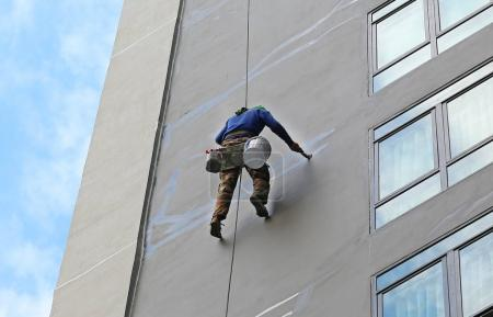 Climber worker hanging on ropes to repair building service on high rise building.