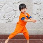 Kid girl in Shaolin monk orange clothes doing Medi...
