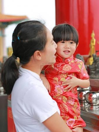 Asian mother and her child girl in traditional dress Putting coins in a monk bowl at chinese temple in bangkok, Thailand.