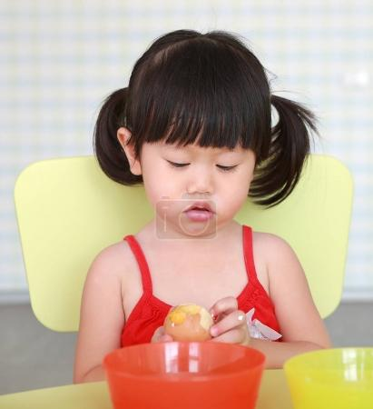 Asian Child girl play and eating boiled egg at living room