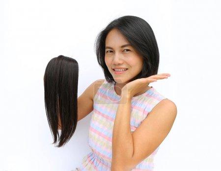Photo pour Femme asiatique donnant ses cheveux aux cancéreux - tenant ses ancien cheveux après une coupe de cheveux, généreusement don de ses longs cheveux pour faire des perruques pour les patients cancéreux qui ont perdu leurs cheveux - image libre de droit