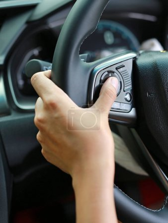 Hand using Car convenient function on steering wheel