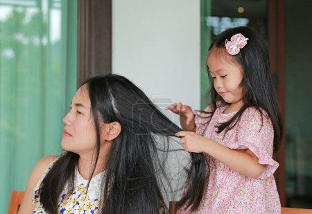 Little child girl coif her mother hair.