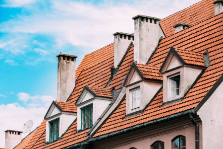 Riga Latvia. Mansard Tile Roof With Four Gable Fronted Dormer Windows On The Old Building Under Blue Sky