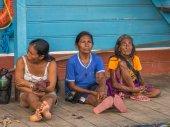 Donna su un molo. Locali donne di età diverse che si siede su un molo nel porto di Amazon river