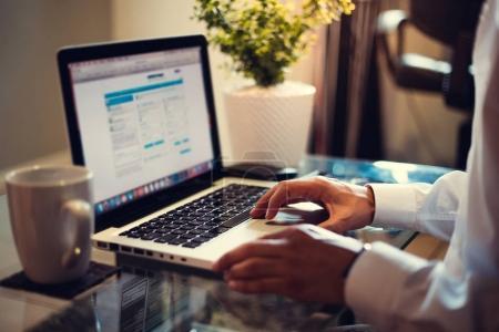 Photo pour Homme d'affaires en chemise blanche tapant sur le clavier de l'ordinateur portable - image libre de droit
