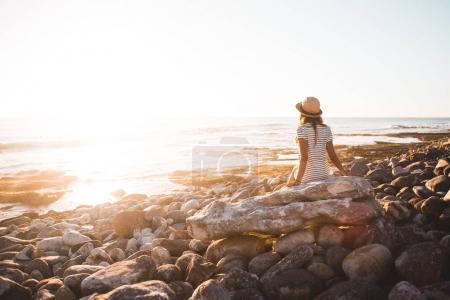 Photo for Young woman sitting on beach rocks at sunset - Royalty Free Image