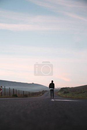Man walking away on asphalt road