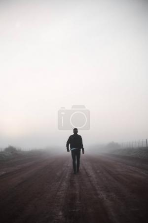 Photo for Man walking away on misty road - Royalty Free Image