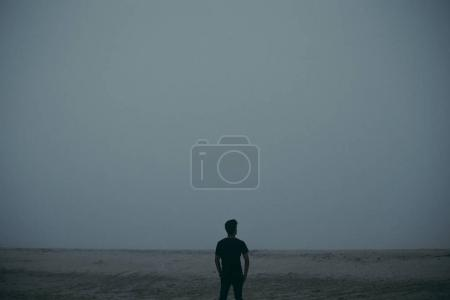 Photo for Silhouette of young man walking on sand in mist - Royalty Free Image