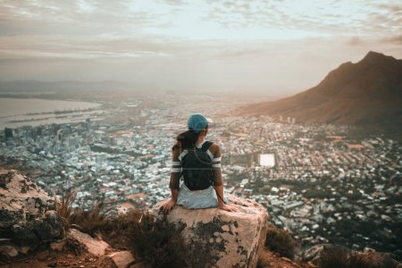 Photo for Woman hiker in mountains above the city - Royalty Free Image