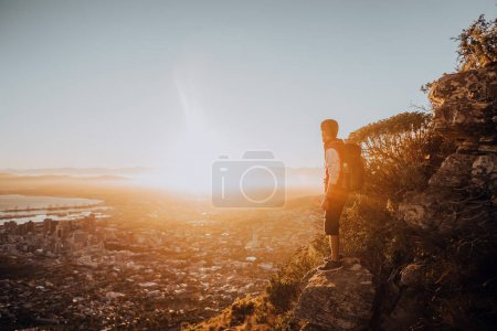 man standing high on rocks