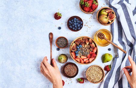 Photo for Top view showing hands eating porridge with honey nuts, blueberries on white wooden table selective focus, blurred background Good morning - healthy breakfast background - Royalty Free Image