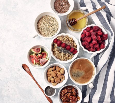 Photo for Healthy breakfast, top view. Oatmeal porridge with raspberries, figs, chia seeds, flax seeds, almonds and pecans, honey and coffee. - Royalty Free Image