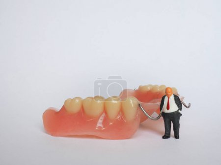 Miniature elderly standing on removable denture, on white backgr